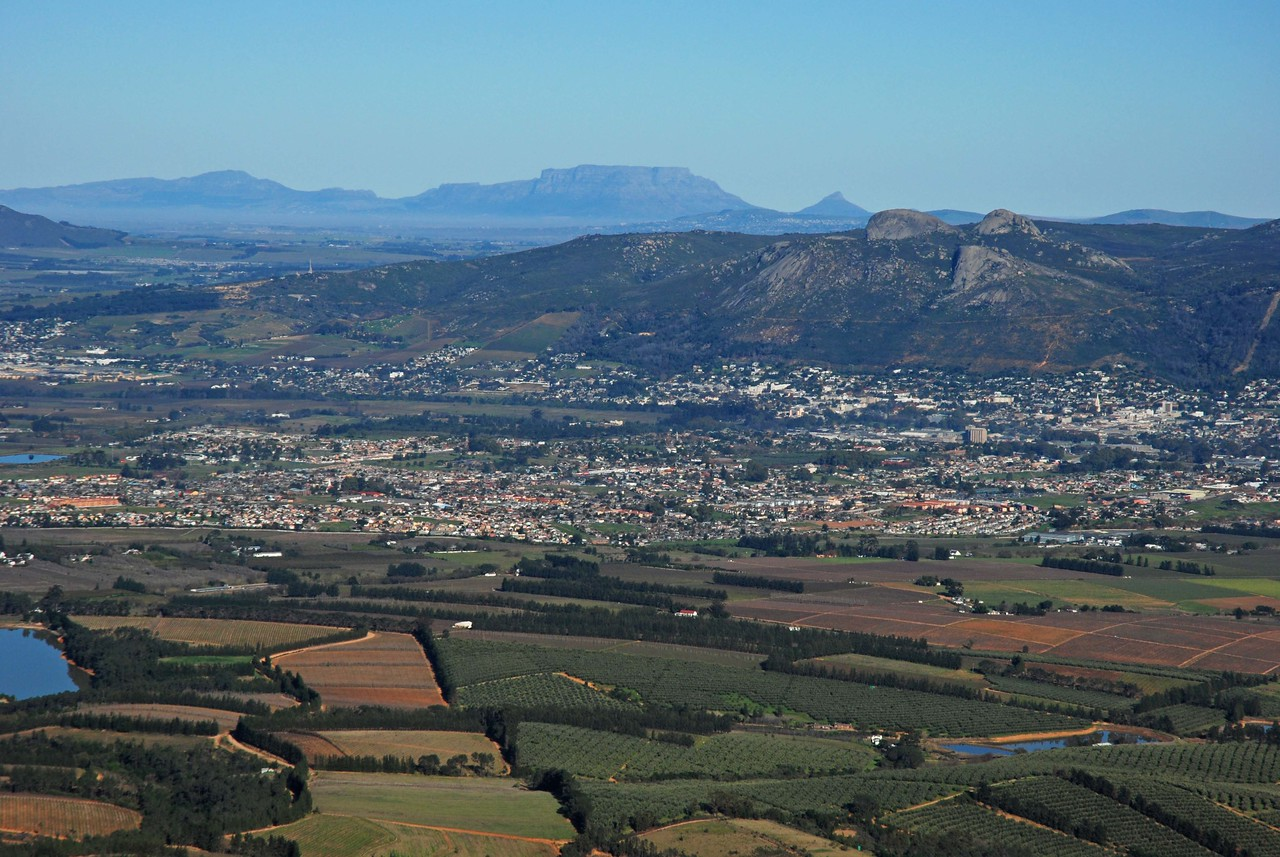 The view from the top of the Du Toit's Kloof Pass - Table Mountain and Lion's Head in the distance, the town of Paarl  and vineyards in the foreground.<br /> <br /> The journey to Kgalagadi Transfrontier Park, where we were to spend twelve nights on safari, is a long one (1078km), but one that is possible to do in a day. However, no matter which route you take, it is a very scenic drive and it is a shame to rush it. We chose to break up the trip with a night in Karoo National Park, which lies 450km to the northeast of Cape Town. We followed the N1 northeast out of Cape Town and climbed through the 820m Du Toit's Kloof Pass, from where the views of Table Mountain and Lion's head were lovely.