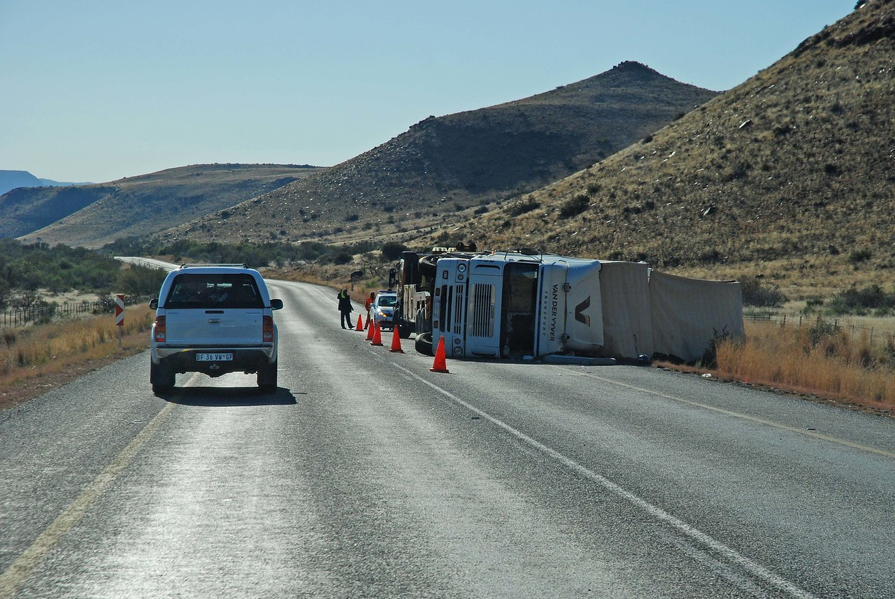 Another casualty of the highways in South Africa<br /> <br /> We passed an 18-wheeler lying on its side, most likely another victim of a highway with narrow, paved shoulders, which truckers and motorists use as a second lane, pulling over onto it to allow vehicles to overtake them - very dangerous at highway speeds if the driver pulls over just a bit too far, and the tires catch the soft gravel beside the shoulder. Of course, this custom of moving over onto the paved shoulder to allow those wishing to pass to do so, even in the face of oncoming traffic, means that it is imperative that drivers watch carefully for oncoming cars doing the same thing, and infringing on their lane. <br /> <br /> In addition to the hazard of vehicles encroaching on your side of the highway, there are the two very different types of vehicles and drivers on South African highways - those who drive at least 20 km under the speed limit (because their poorly maintained vehicle isn't able to go any faster), and those that drive at least 20 km over it (the BMWs and Mercedes).  This makes driving at the speed limit rather frustrating (continually having to pull out to pass), and dangerous (speeders suddenly appearing on your bumper). Highway driving in South Africa requires your full attention, and is not often a terribly relaxing experience!