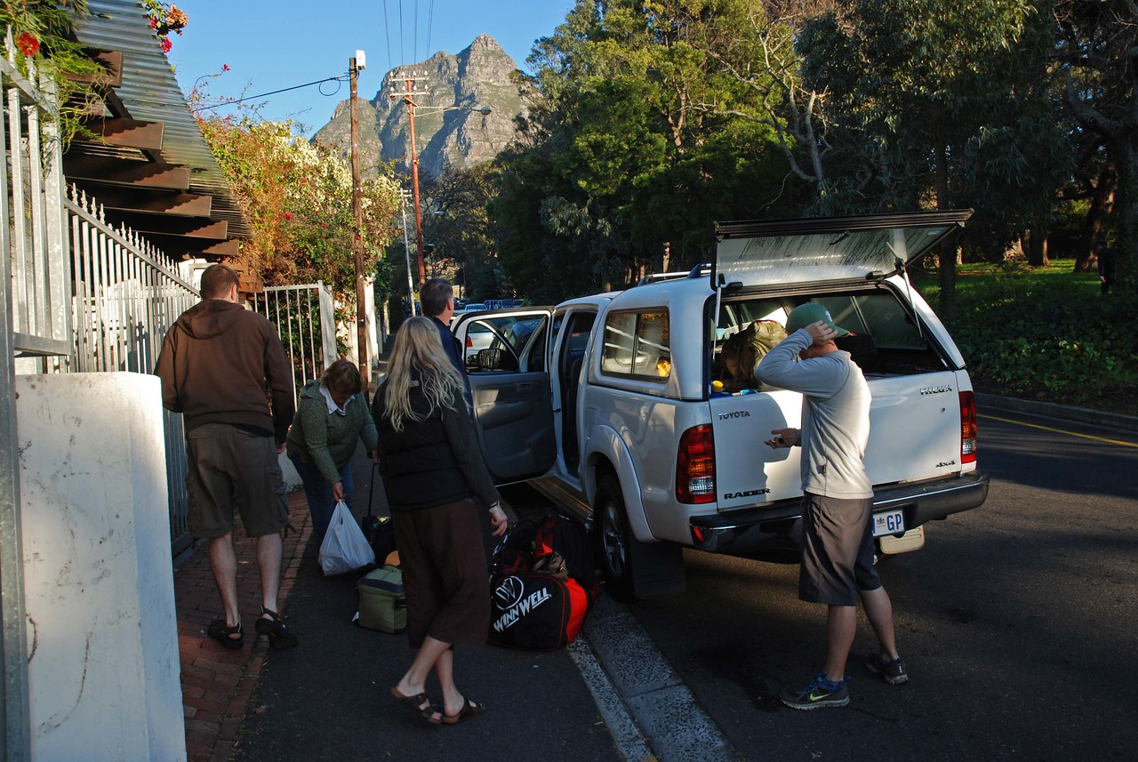 Graham, Kathy, Laura, Jim and Craig loading one of 4x4s on the street outside our home in Cape Town, Table Mountain visible at the top of the street<br /> <br /> The afternoon before we left Cape Town for our safari in Kgalagadi Transfrontier Park, we picked up two Toyota Hilux double cab 4x4s from the Avis outlet at the airport. For those of us who had been driving a little Honda Jazz for the past month, the 4x4s seemed enormous. We packed all but our computers, cameras and other electronics into them later that evening, including two weeks worth of food, water and wine, duffles with our clothing, a braai grill and charcoal and everything else that we needed to be completely self-sufficient while camping in the park. Laura took charge of organizing all the food into large plastic tubs, while Craig, the acknowledged packing expert (from his student days working at Costco), was in charge of fitting everything into the vehicles. We looked mighty organized by the time we retired for the night, and I couldn't wait to get underway in the morning. <br /> <br /> We parked one 4x4 on our driveway and the other at the B&B that Jim and Kathy were staying at. There is so much security in both our neighbourhood and the community in which the B&B is located that we felt they quite comfortable leaving the packed vehicles unattended overnight. <br /> <br /> In the morning, after a quick breakfast, we threw the remainder of our belongings into the 4x4s, sorted out who would travel in which vehicle (there were various configurations tried out during the trip such as adults vs. kids, girls vs. boys, avid birders vs. the not-so-keen-on-birds types, one family vs the other etc.), and were on the road by 9:00am. It was a clear, warm morning, and the view of Table Mountain as we drove north out Cape Town was lovely.