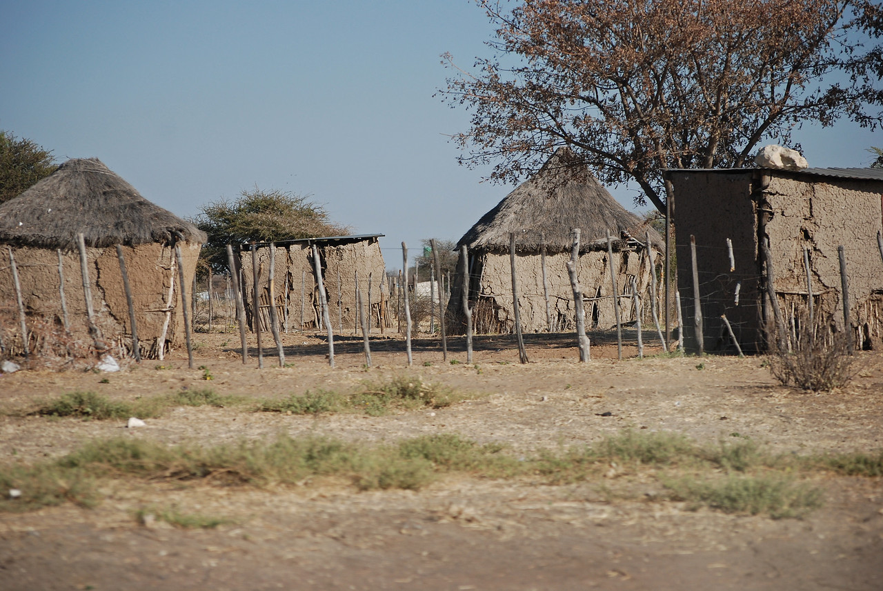 Village houses along the highway near Gobabis<br /> <br /> From Gobabis, we continued east on the B6 for 120km to Buitepos, the Namibian border post. We saw two lilac-breasted rollers, surely one of southern Africa's prettiest birds with its brilliant blue wing feathers and lilac throat and breast. We also saw several pale chanting goshawks perched in thornbushes which, while admittedly very pretty with their coral pink legs and white upper wings, we had grown very tired of while visiting South African parks. <br /> <br /> About 20km west of the border, having not encountered a picnic site for many kilometres, we stopped for a very late tea break at the entrance to Zelda's Guest Farm. We arrived at Buitepos just after noon and were only at the border post for about ten minutes, long enough to have our passports stamped, names dutifully entered into a computer, and to fill out immigration forms confirming that we were indeed leaving Namibia.