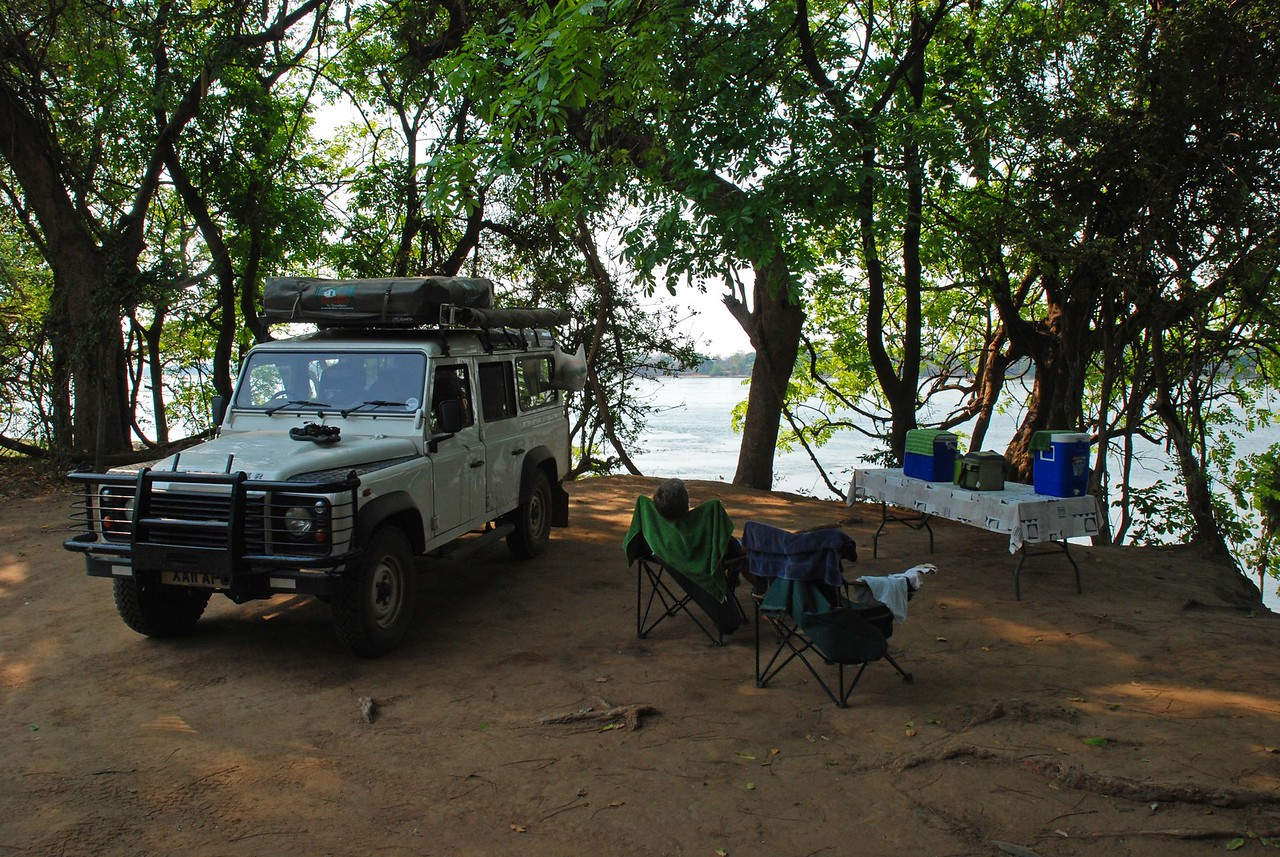 Elly Campsite at Mvuu Lodge<br /> <br /> Elly campsite at Mvuu Lodge, just outside of Lower Zambezi National Park in Zambia. The site was on the banks of the Zambezi, with an unobstructed view of the river, Mana Pools National Park in Zimbabwe on the opposite bank, pods of hippos, elephants crossing the river, and many species of birds. Soothing music, in the form of hippos grunting and frogs ribbiting, played continually in the background. At night, we heard lions roaring, hyena calling, elephants trumpeting, baboons barking and drumming from across the river in Zimbabwe. We woke one morning to find a vervet monkey sitting on the roof of the Land Rover, next to our tent. Of the four campsites at Mvuu, Elly was furthest from the lodge, and very quiet and private. The campsite's biggest asset, however, was the fact that elephants like to use Elly to access the river, so they were frequent visitors to the campsite.