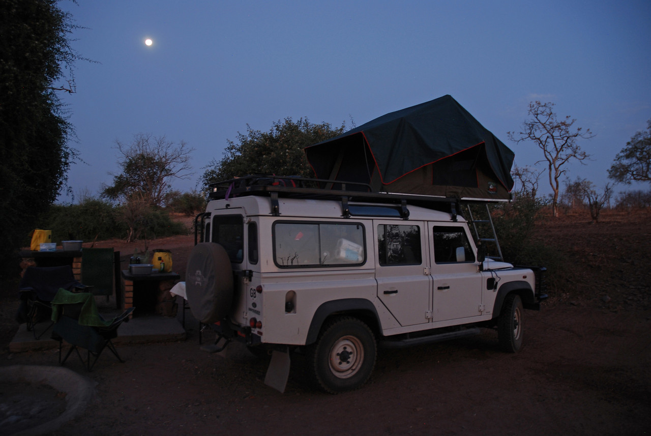 """The Land Rover and the roof-top tent under a full moon at Ihaha campsite in Chobe National Park<br /> <br /> The 2011 Land Rover Puma TDCI, which was named """"Ranulph"""" after British adventurer Ranulph Fiennes. The vehicle had only 15,729km on it when we received it. It was our home for six weeks, and was fully equipped with everything we needed. It took us safely through Namibia, Botswana and Zambia, including along a route near Lower Zambezi National Park in Zambia that was listed as """"not recommended"""" on Tracks4Africa. <br />  <br /> We loved the roof top tent, which was very comfortable and cosy, and protected us from torrential rains, gale force winds, and the many elephants, hippos and predators that wandered through our campsites during the night. It came with sheets, a duvet, four pillows and extra blankets - no roughing it here!"""